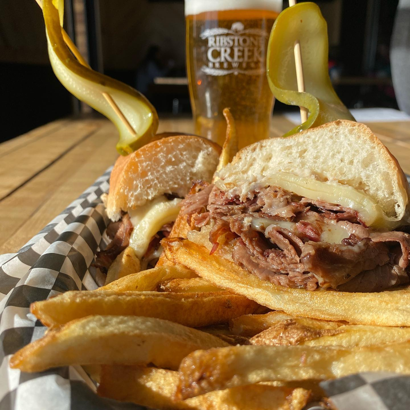 A beef melt sandwich with pickles and fries in front of a pint of beer.