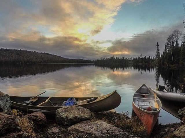 Two canoes sitting on a rocky shore with a calm lake reflecting the clouds in the sky at sunset.