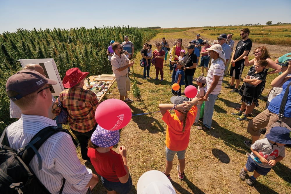 Adults and children listening to a demonstration on hemp farming.
