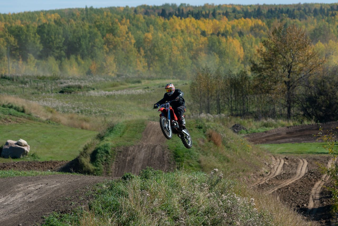 Airborn dirt bike rider making a jump on an outdoor skills course.
