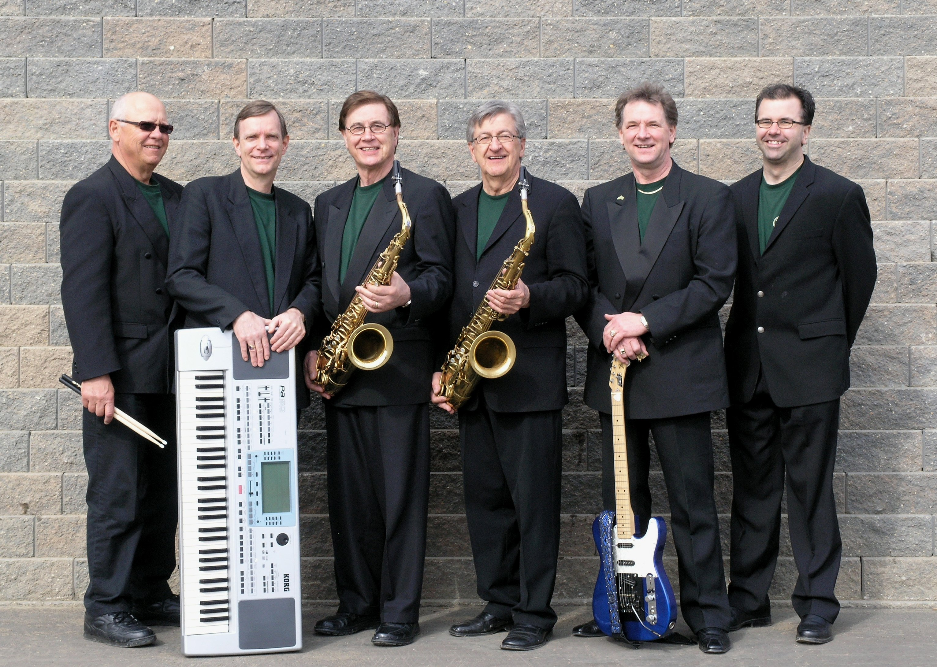 6 members of The Emeralds polka band wearing black suits and emerald green shirts holding their instruments.