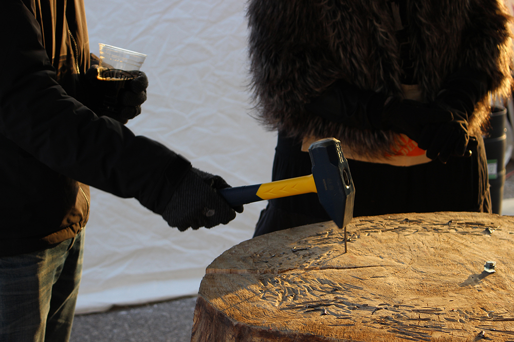 A player of the game Hammerschlagen holding a beer as they try to hammer a nail into the wood stump.