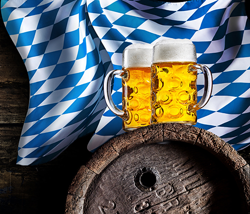 Two pints of beer atop an aged beer barrel with traditional royal blue diamond check Oktoberfest tablecloth hanging behind.
