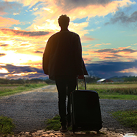 A silhouette of a man with luggage walking towards a sunrise.