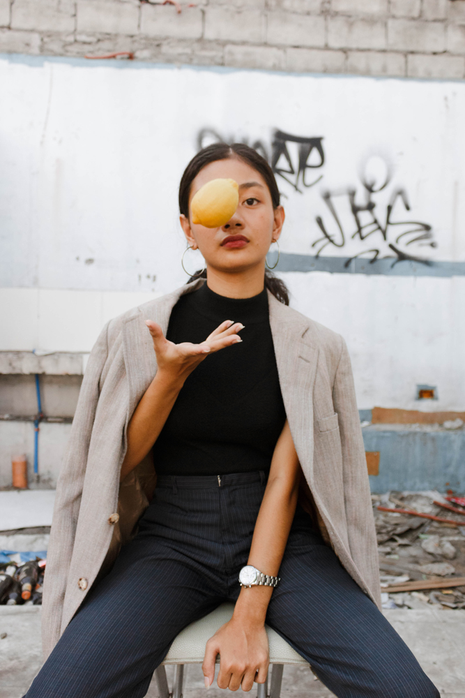woman sitting while throwing a lemon which covers her face