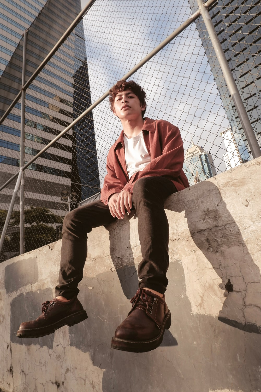Young man sitting on wall before a fence looking in the camera with a serious face