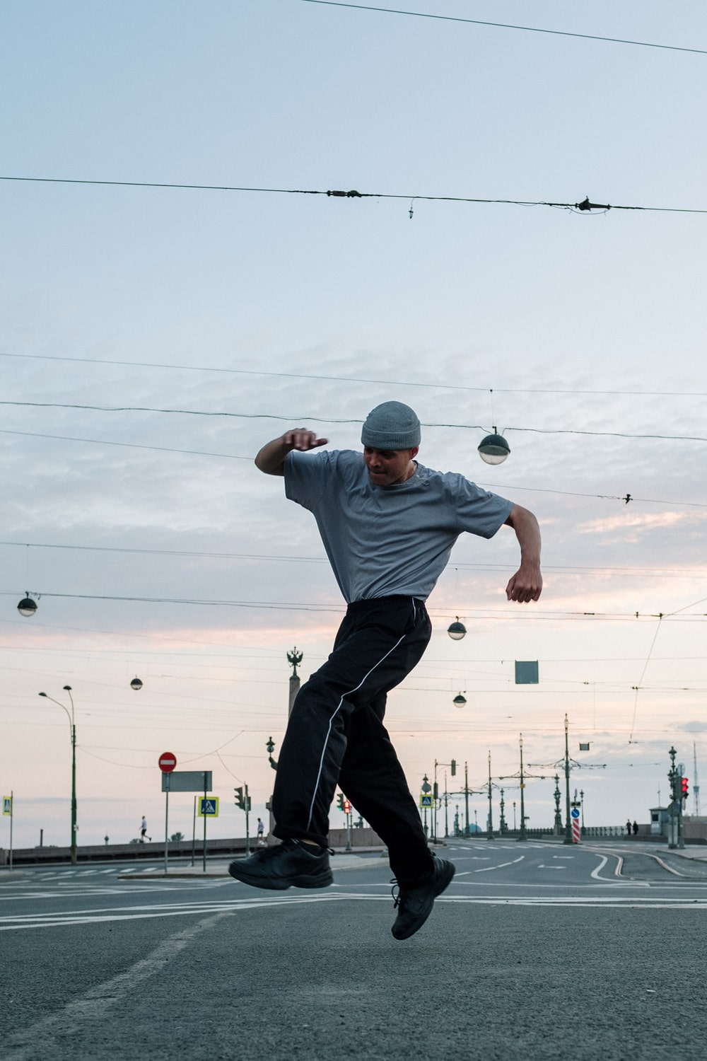 man jumping on the street with a sunset in the background