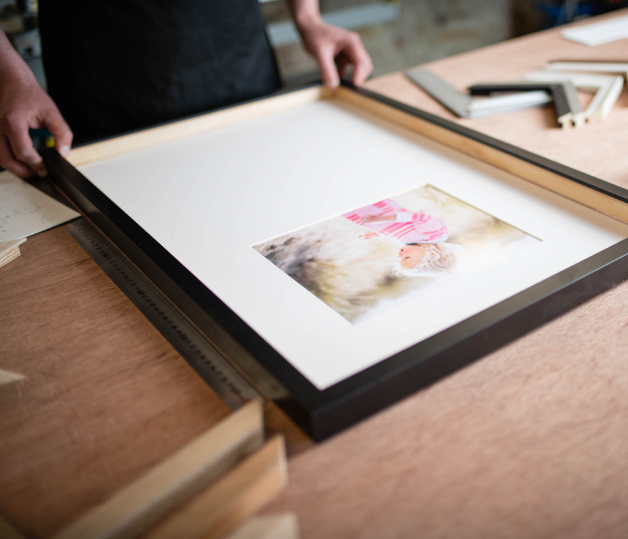 A picture framer is putting a frame together in a workshop.