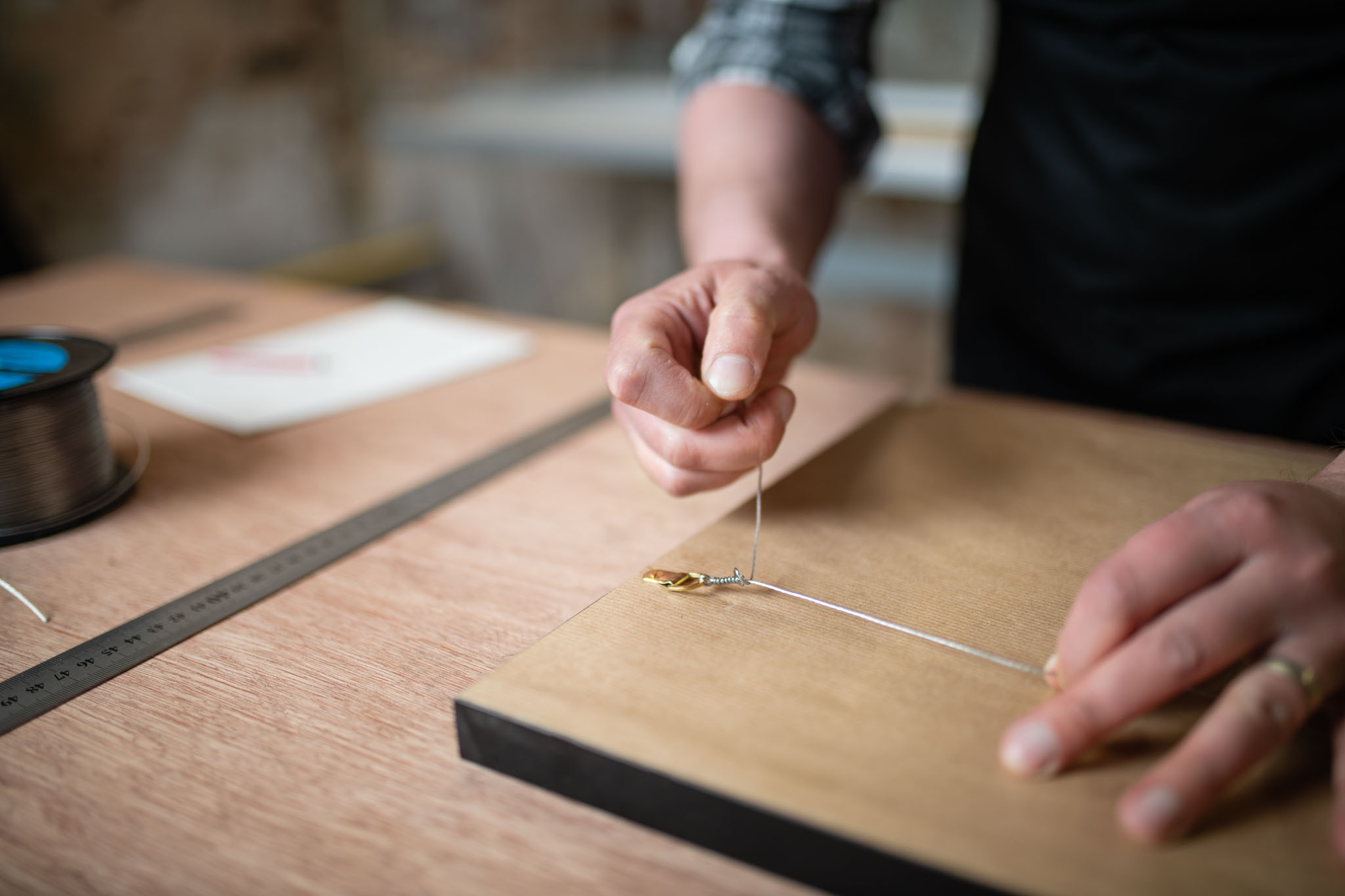 a male picture framer putting the wire on the back of a frame.