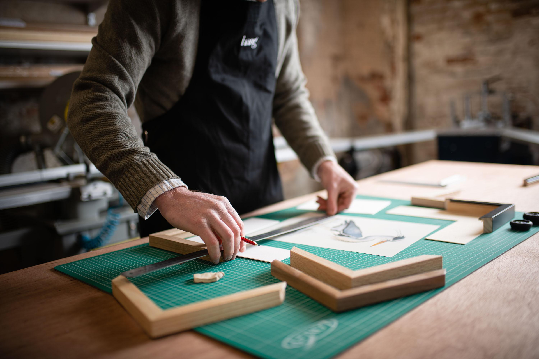 A picture framer making a custom frame.