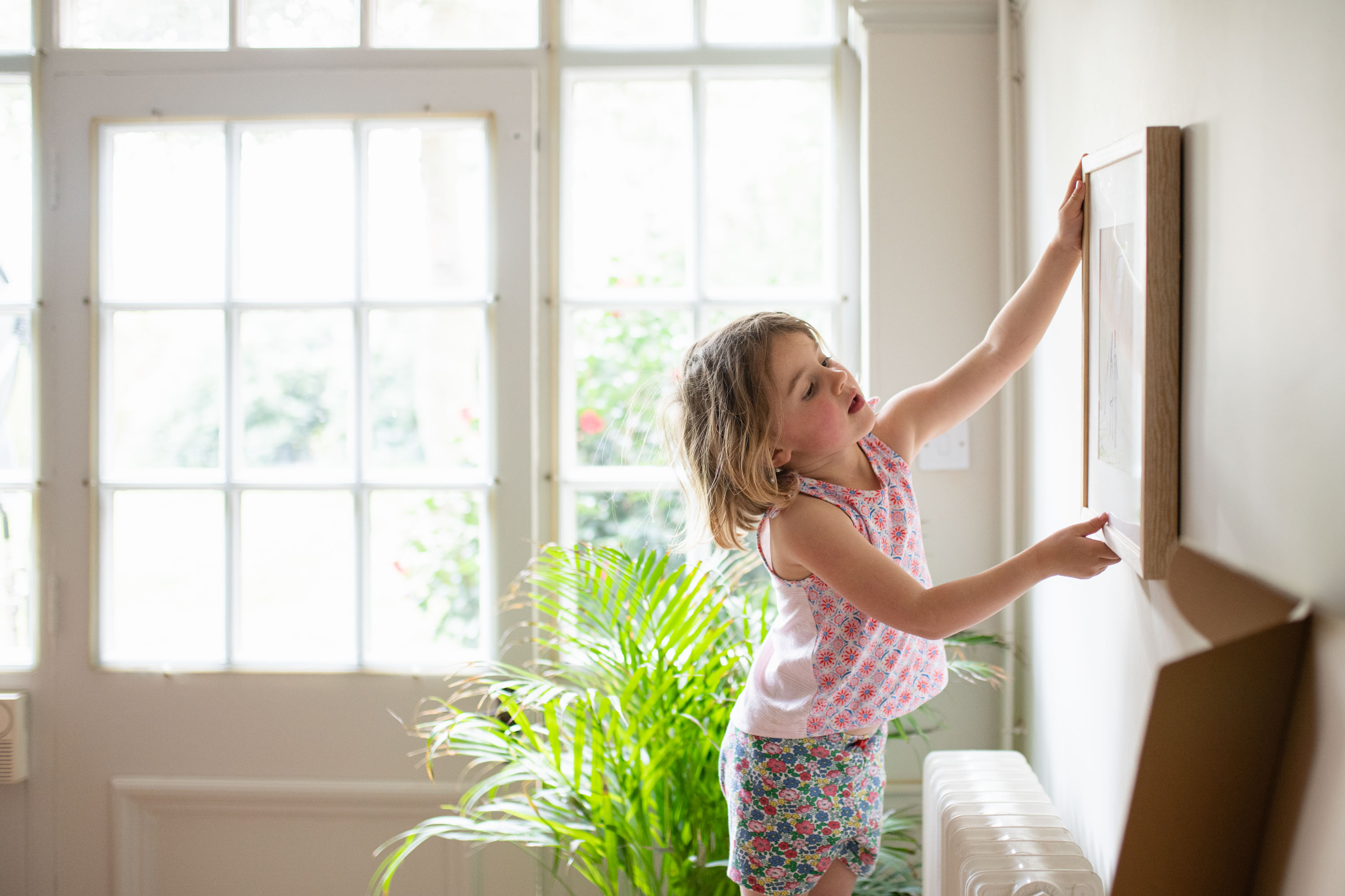 A young girl hanging a picture frame