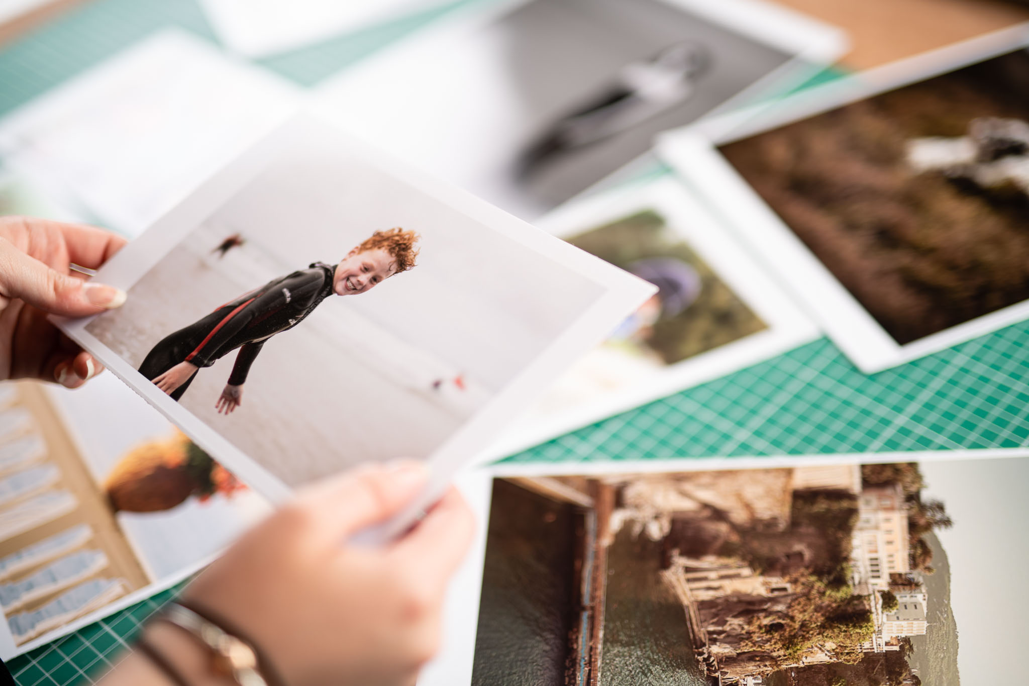 closeup photo of a woman hands, holding a photograph. There are photographs on a table.