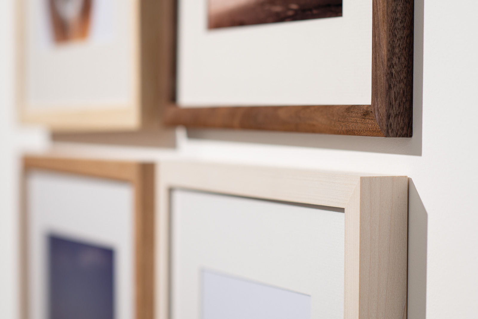 close up photo of four hardwood picture frames on a wall.