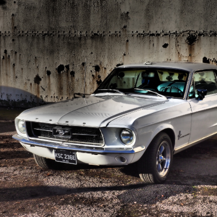 An old ford mustang car in front of an old hanger door