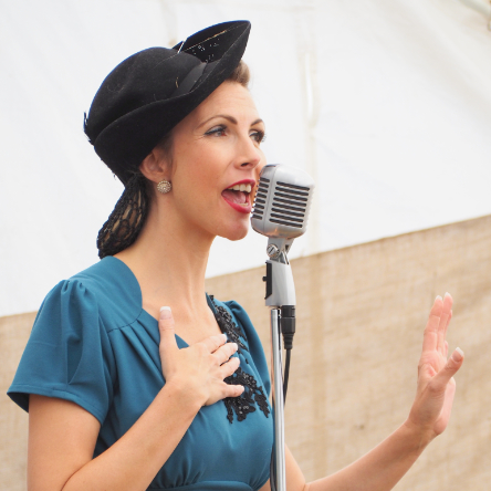 Lady in world war two outfit singing into a WW2 microphone
