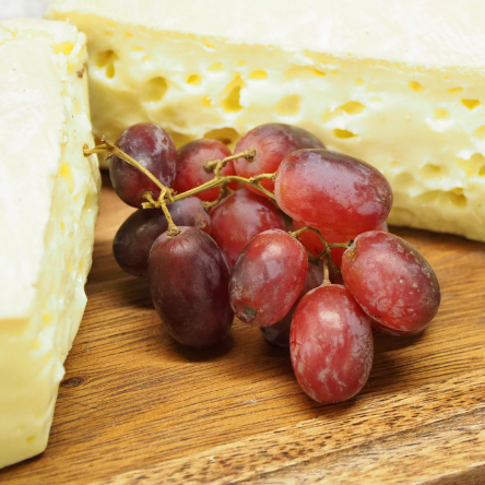 Red grapes in between some Brie cheese
