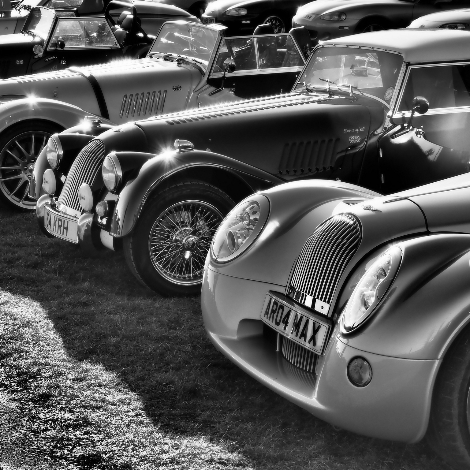 Black and White Picture of selection of old cars in a row with sun glistening from their bodywork