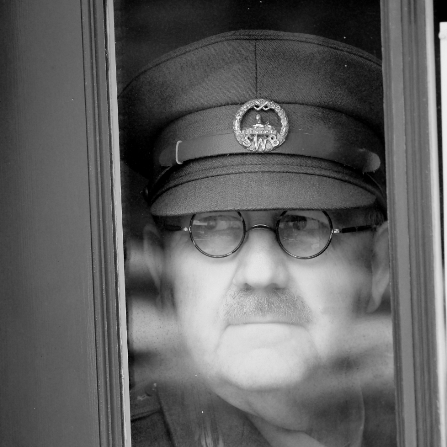 Black and white picture of a man dressed in world war two British officers uniform, looking out of a train window