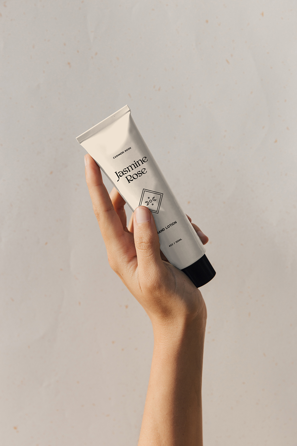 A hand holding branded hand lotion