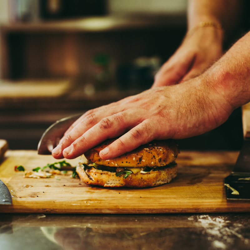 chief cutting burger in half