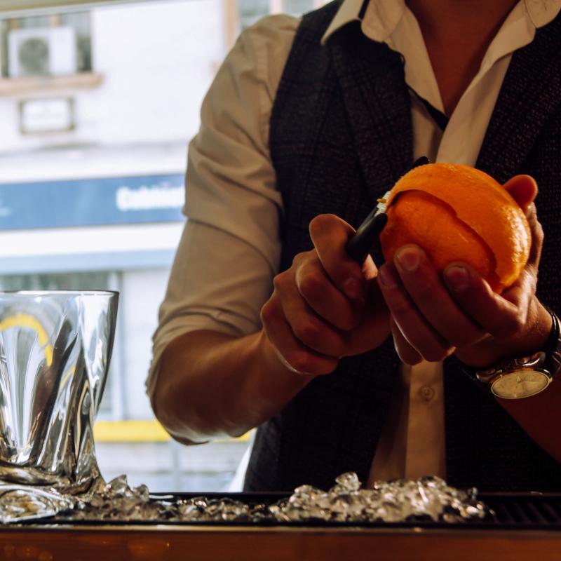 bartender cutting zest of an orange