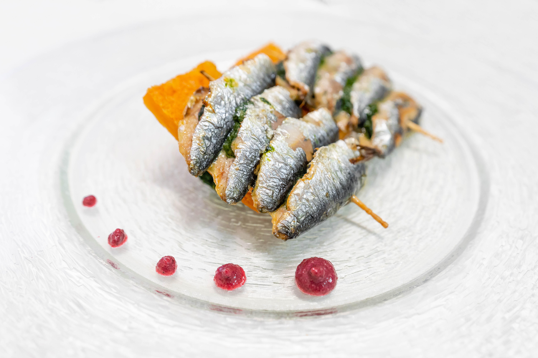 Sardine gratinate con spinaci, pinoli, uvetta, finocchietto e cialda di ceci, all'Osteria Torre di Populonia, ristorante di pesce a km zero in Toscana.