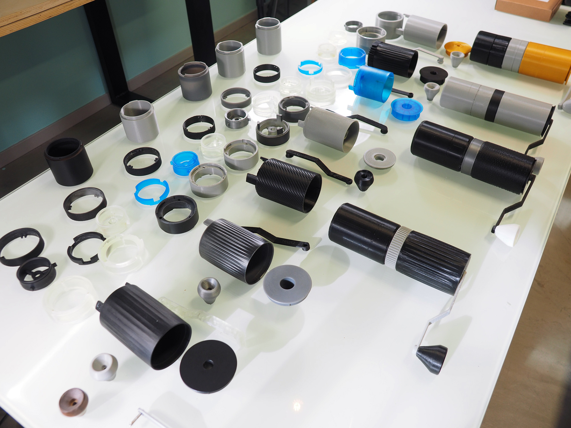 Various stages of HIKU prototypes on a table, laid out in chronological order.