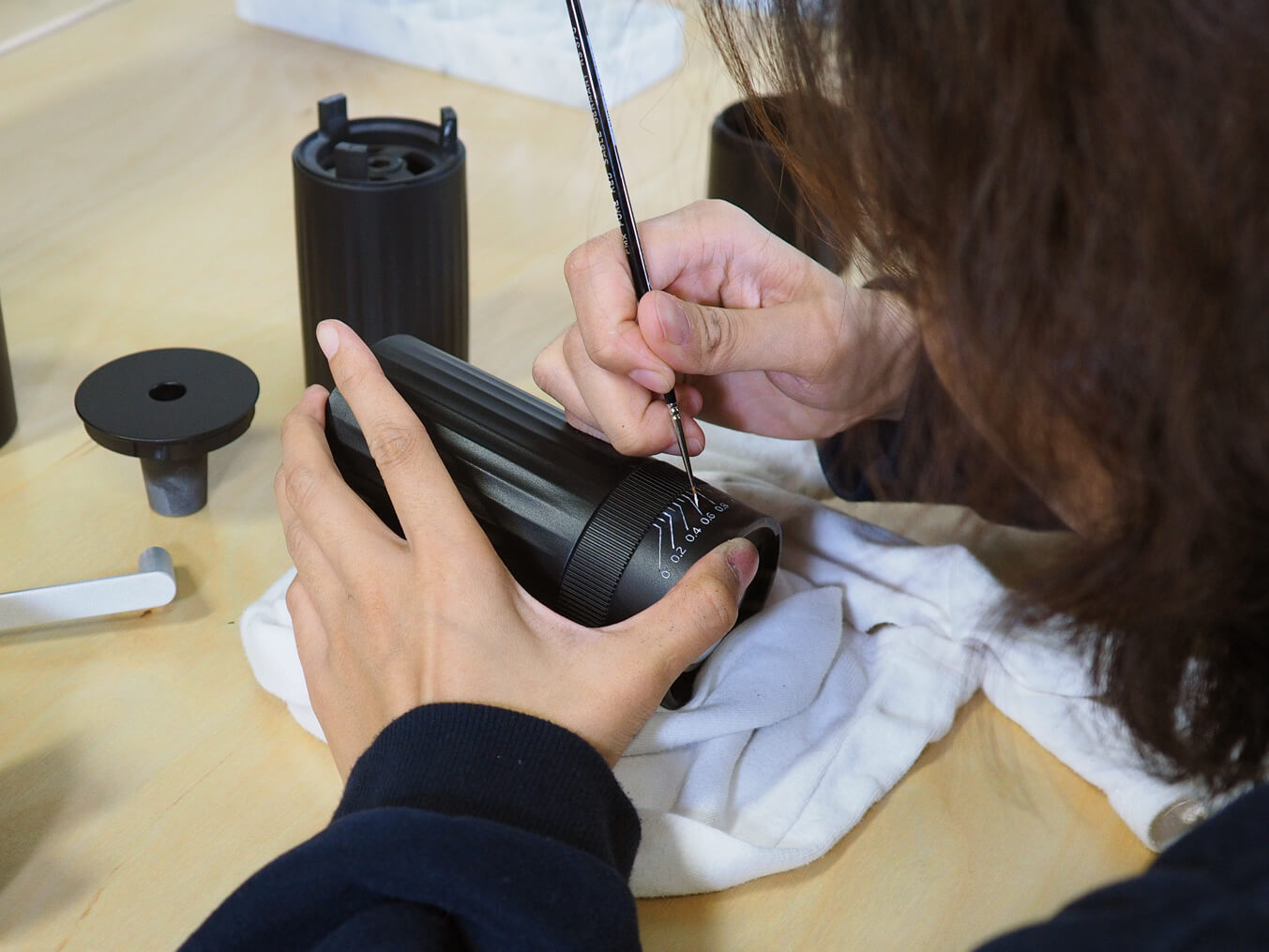 Carefully painting the grind measurements by hand on a prototype of the HIKU hand coffee grinder.