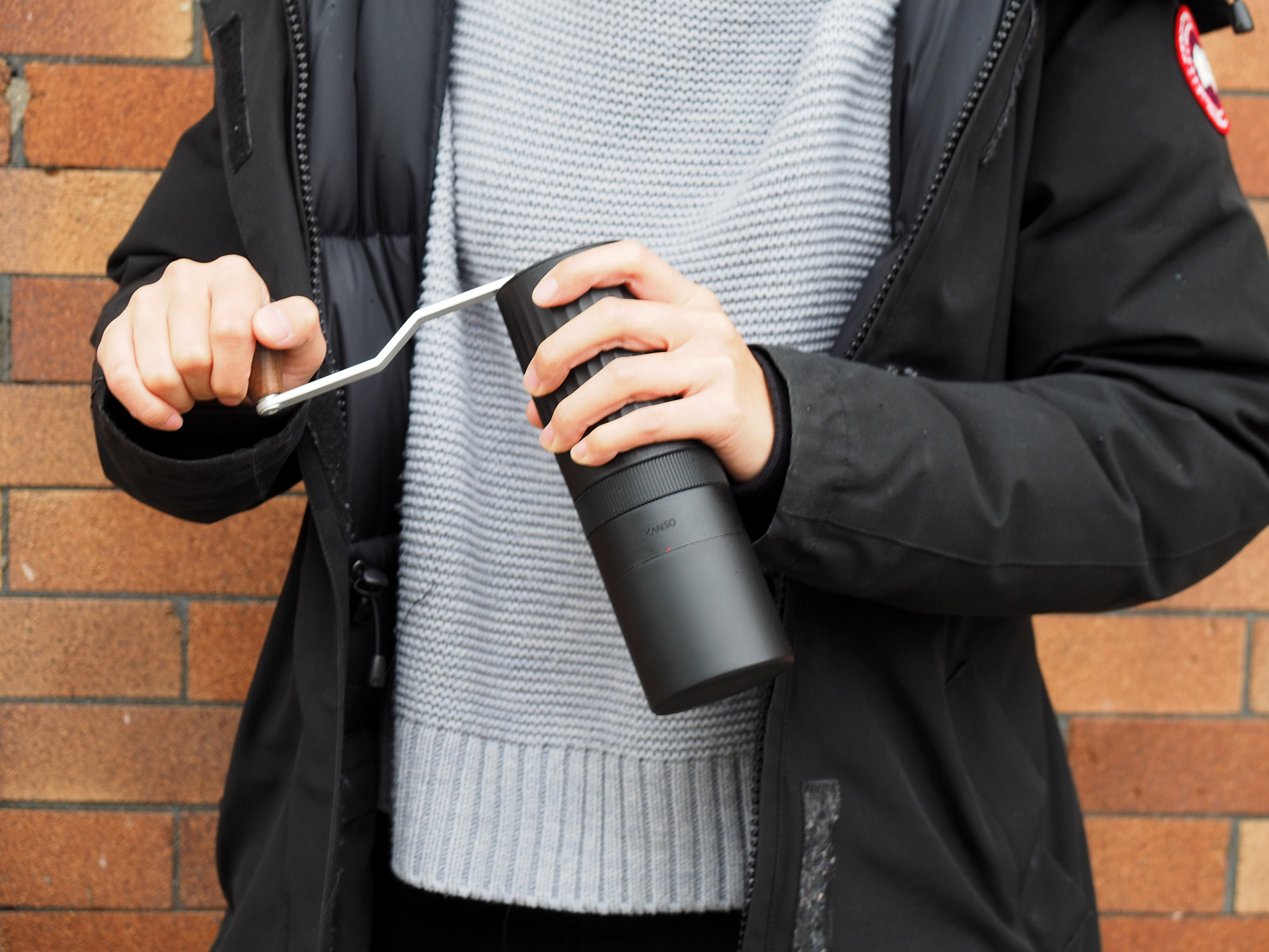 A woman holding the HIKU hand coffee grinder, gripping the handle like she is grinding coffee.
