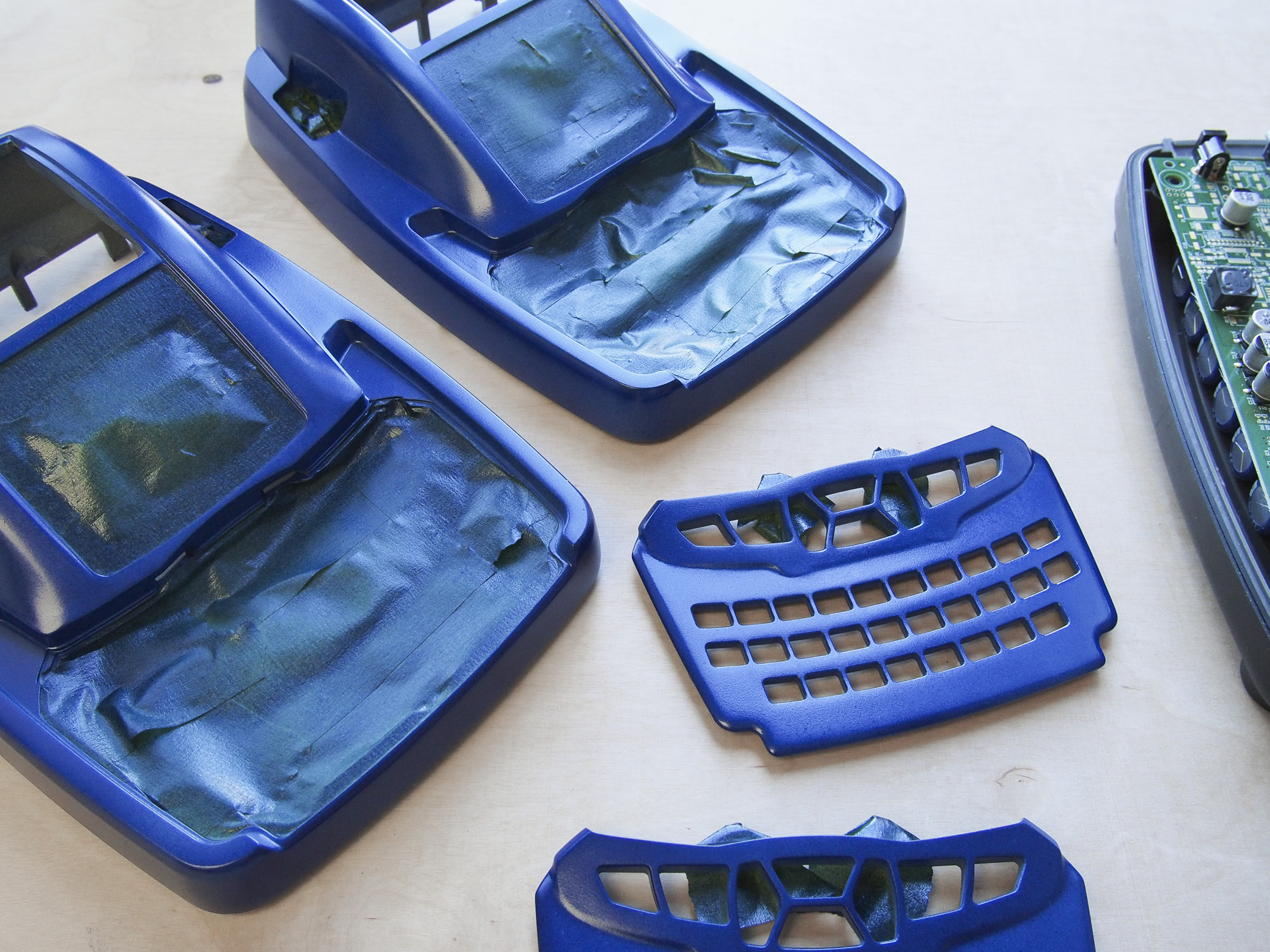 Various enclosure parts of the CADEX Spectro Rapid Battery Analyzer in blue.