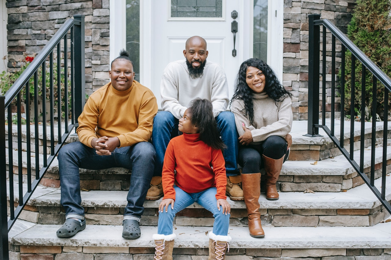 A family of four posing on the steps of their front porch