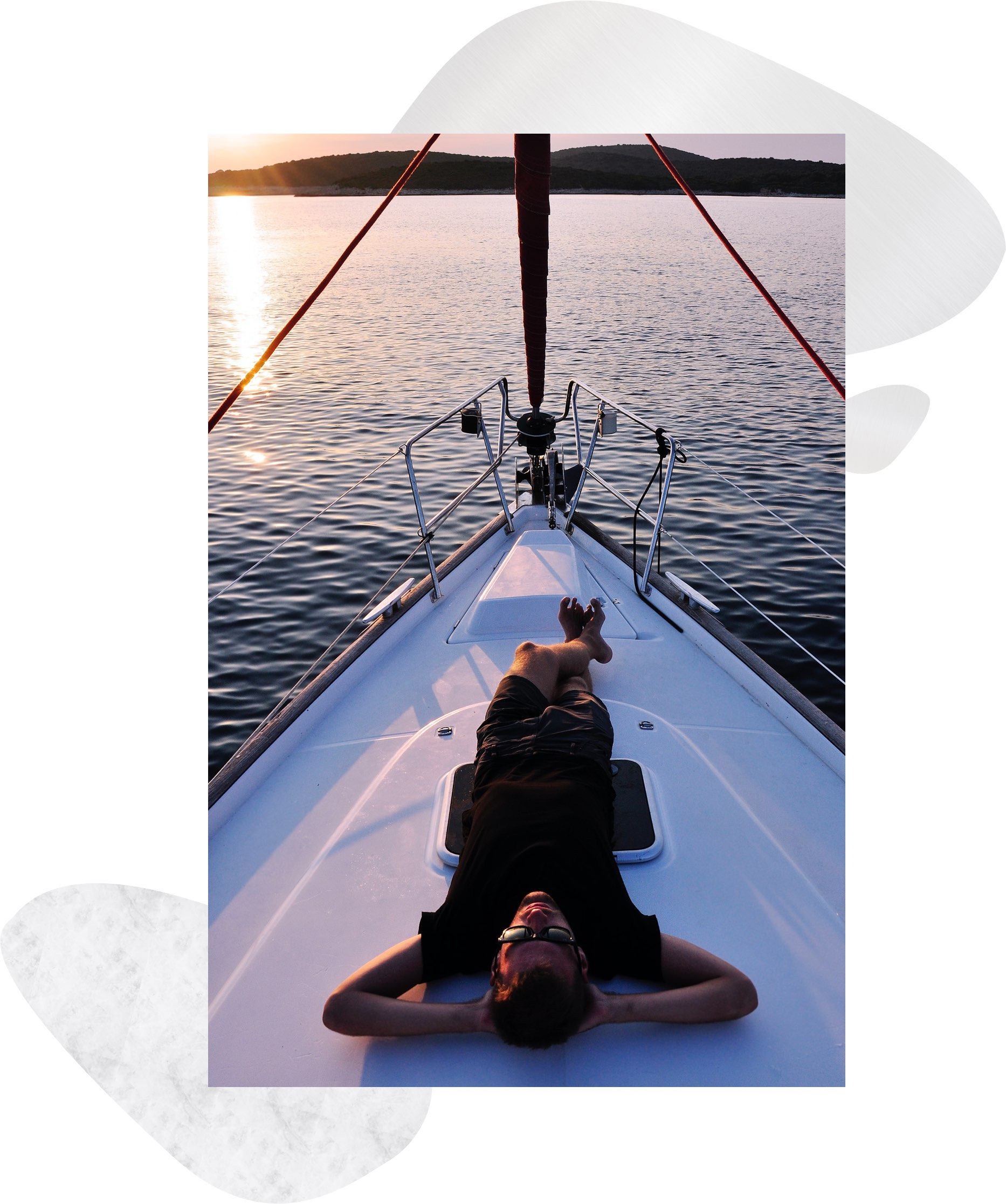 a man laying down on a sailboat