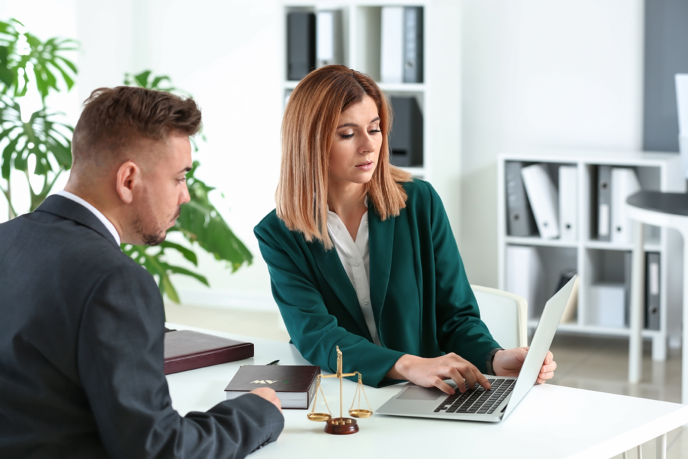 a man and woman looking at a laptop