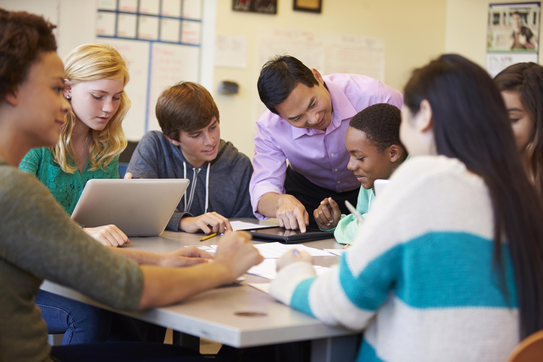Leraar legt iets uit aan een leerling in de klas.