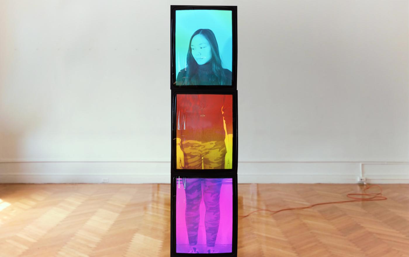 A video sculpture by Benton C Bainbridge portrays Allyssa Jill across 3 stacked CRT monitors in a gallery.