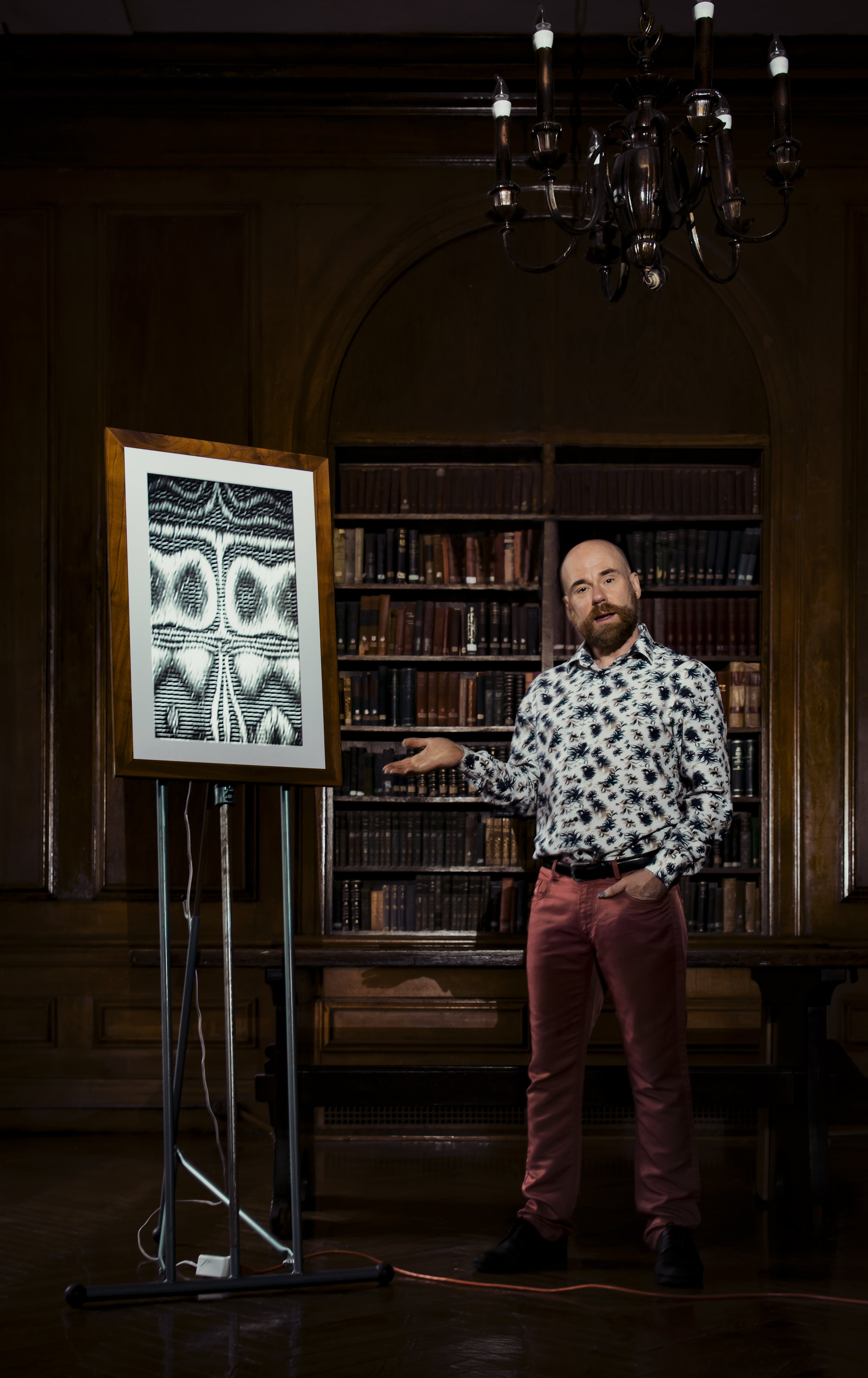 Media Artist Benton C Bainbridge stands in a wood-paneled library next to an easel which holds a framed screen displaying his abstract artwork.