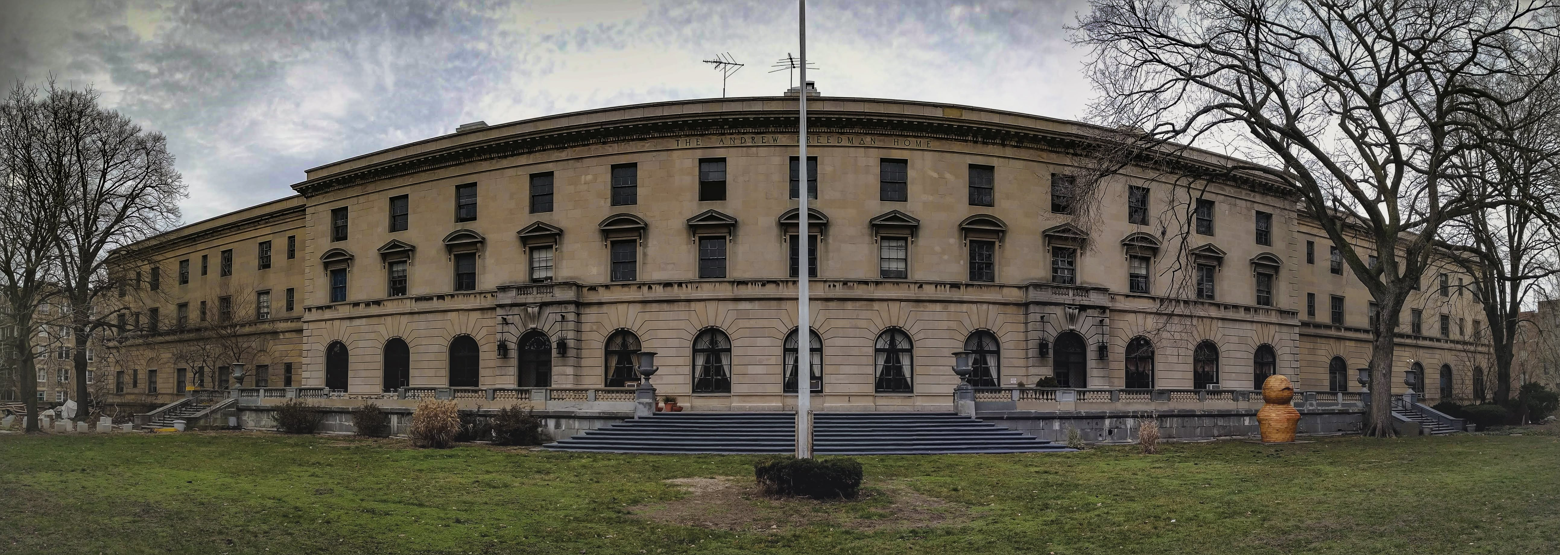 A panorama showing the entire facade of The Andrew Freedman Home as seen from its lawn that fronts the Grand Concourse.