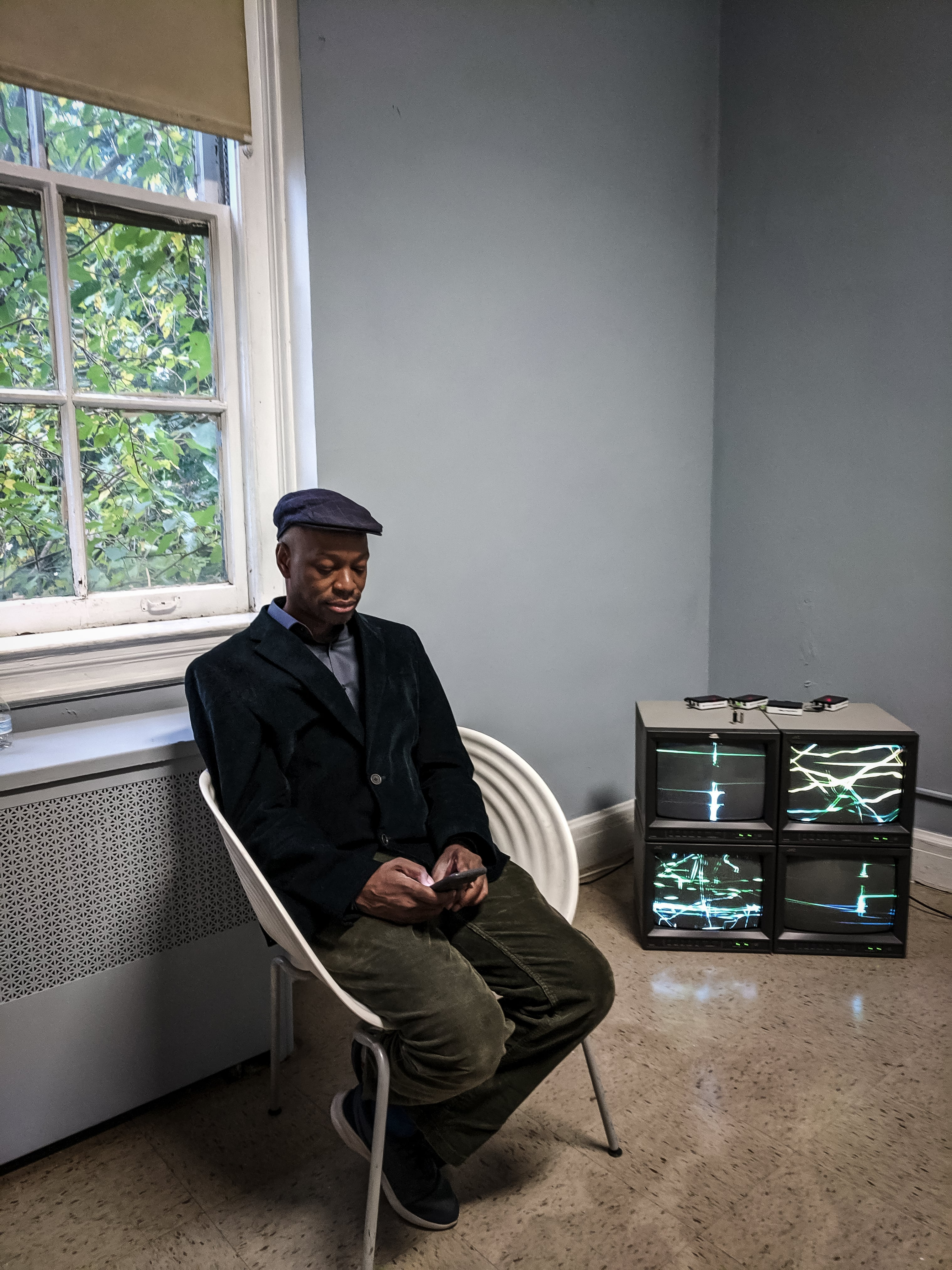 Walter E. Puryear sits in a chair, holding a phone in both hands, with a video sculpture on 4 CRT monitors showing abstract green, calligraphic lines.