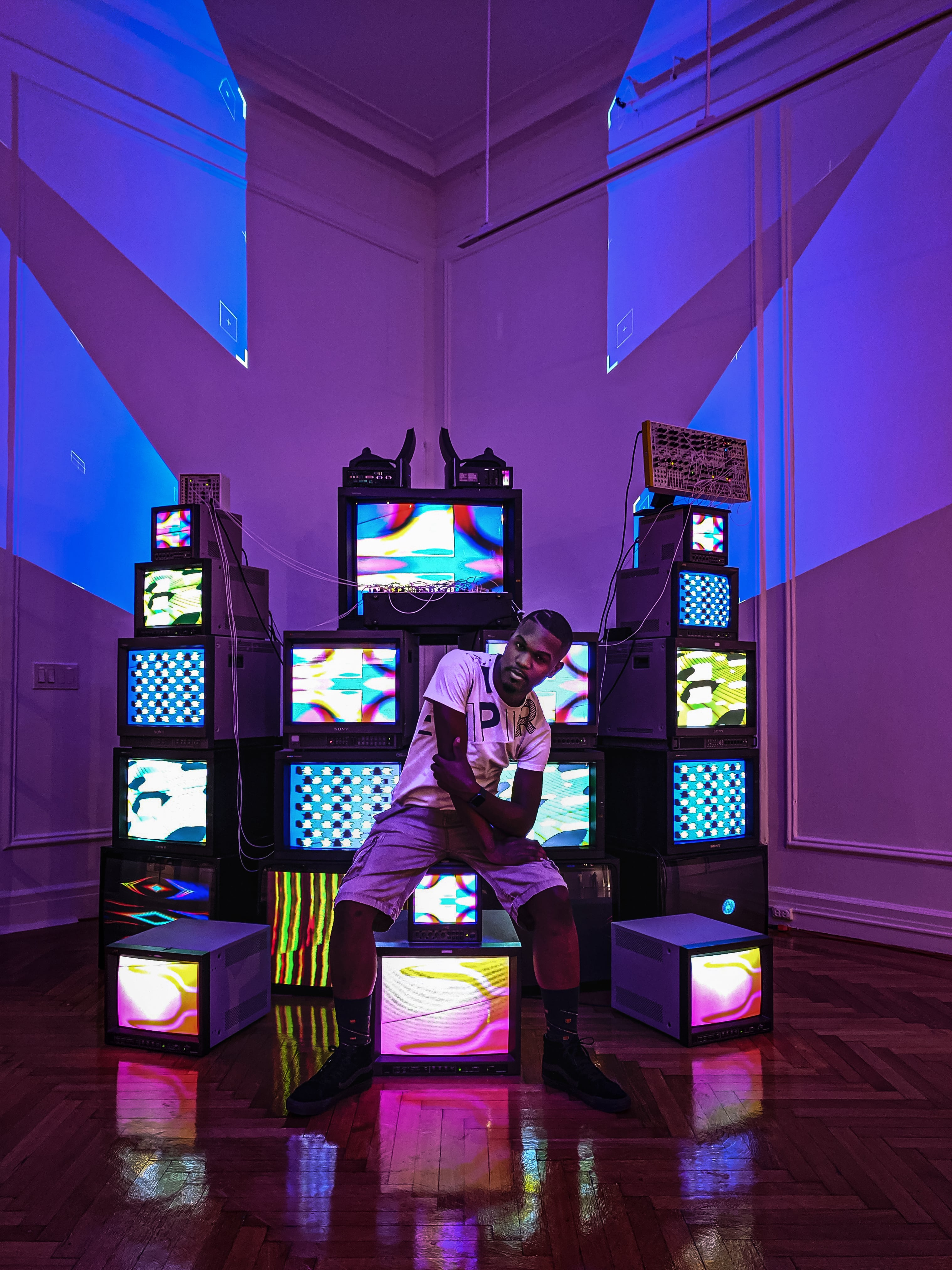 Beauteous—a video sculpture with two dozen screens showing colorful abstract patterns—is seen with a young performer sitting atop the CRTs.