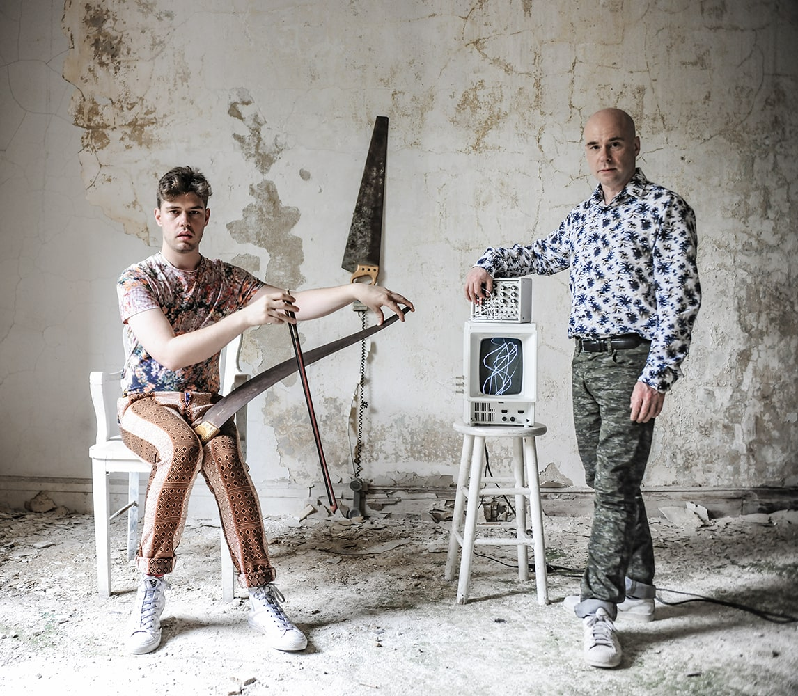 In a room where peeling plaster blankets the floor, Gryphon Rue sits and plays a saw with bow while Benton C Bainbridge stands, playing electronics to generate a squiggly light drawing.