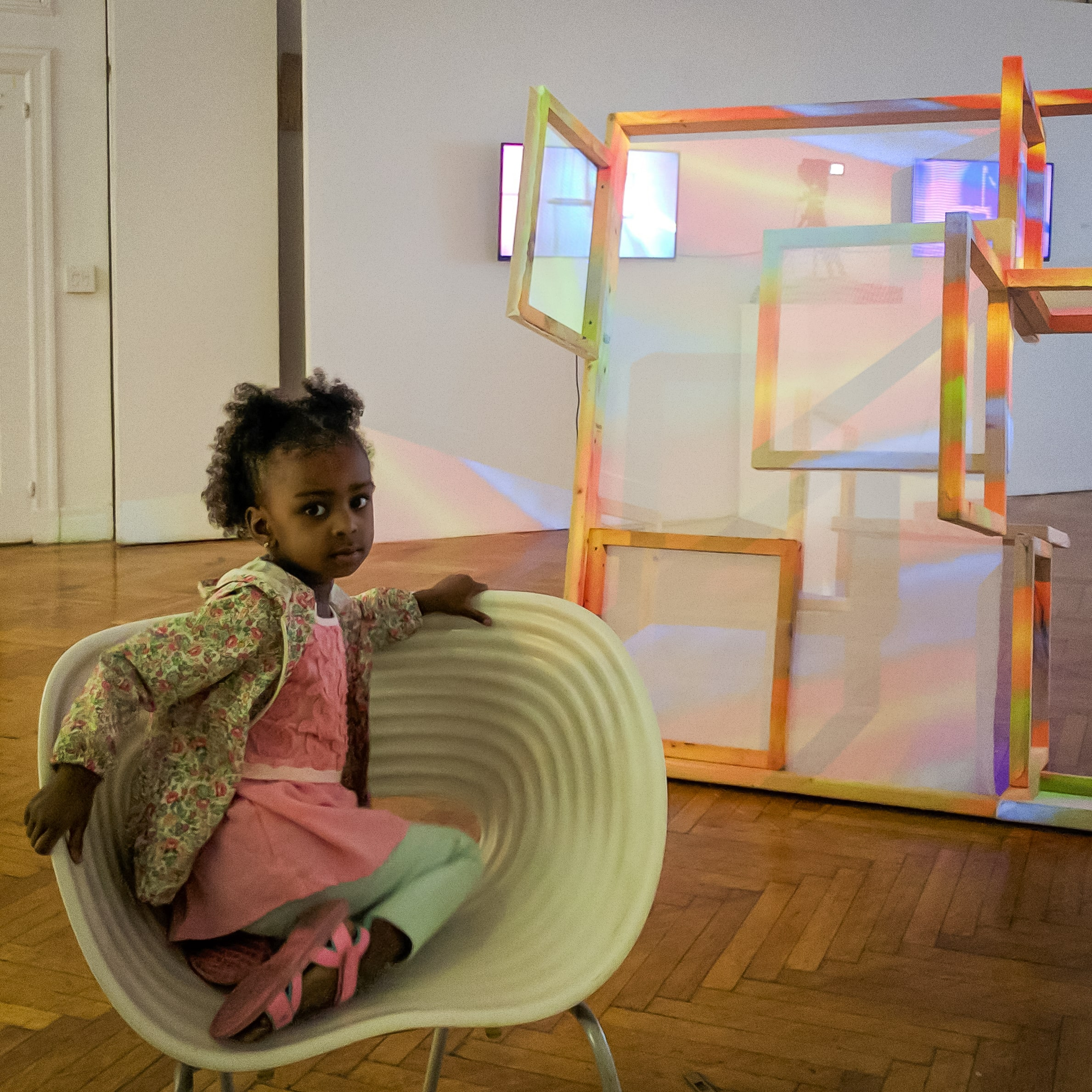 A young girl sits in an exhibition at Andrew Freedman Home in front of a projection mapping sculpture by Benton C Bainbridge and Xavier Figueroa.
