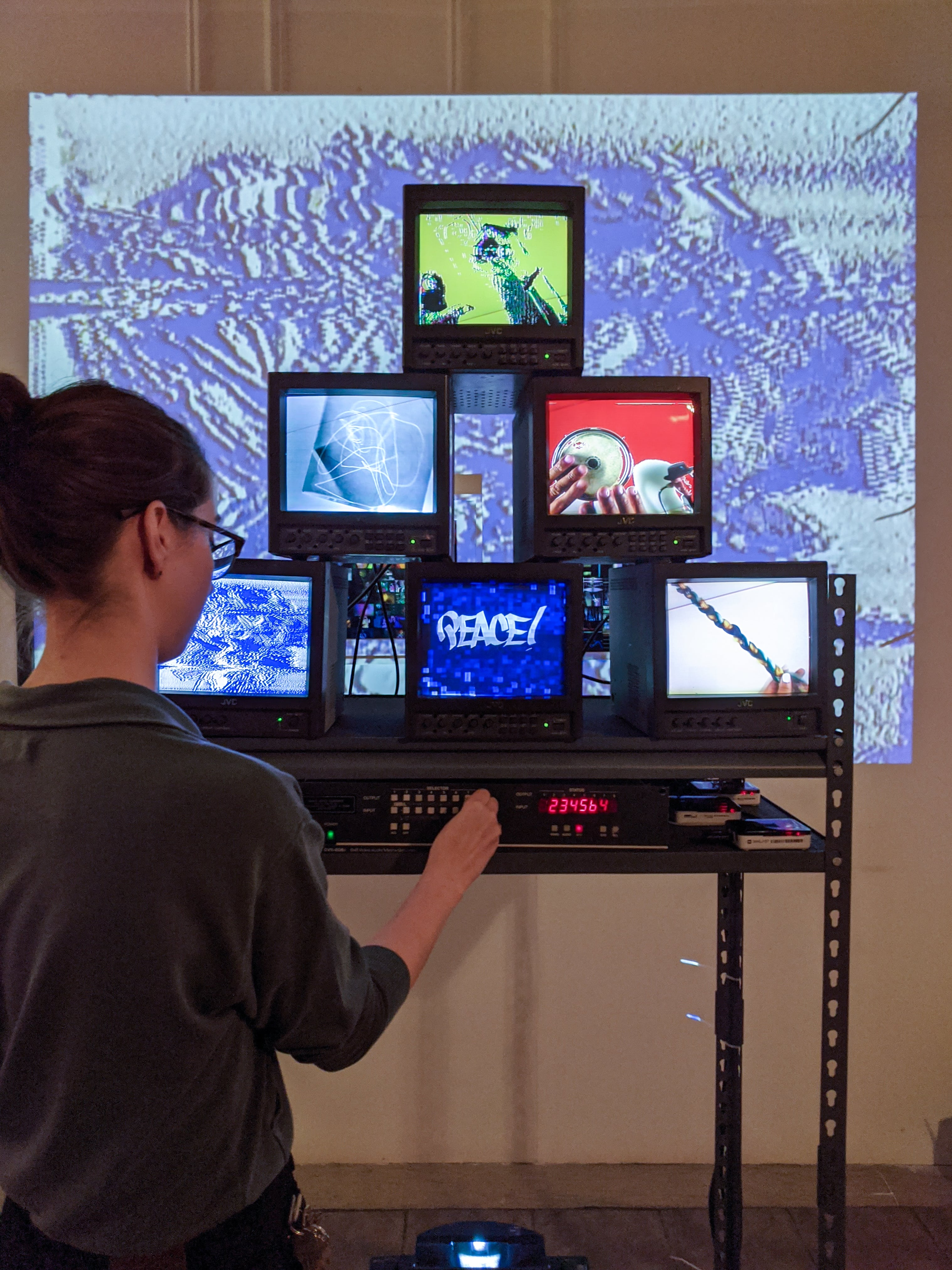 Elena B. Hall puts finishing touches on a video sculpture, with screens displaying colorful media art by various AFH AIR artists.