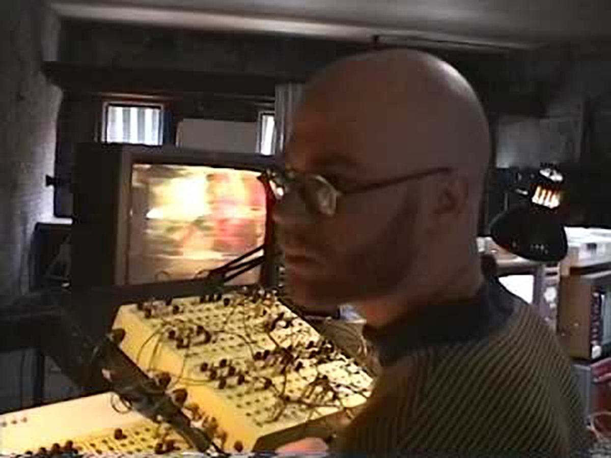 A frame from a document video by Hank Rudolph shows Benton C Bainbridge operating the image processing synthesizers at Experimental Television Center in 1999 during a realtime media improvisation with NNeng.