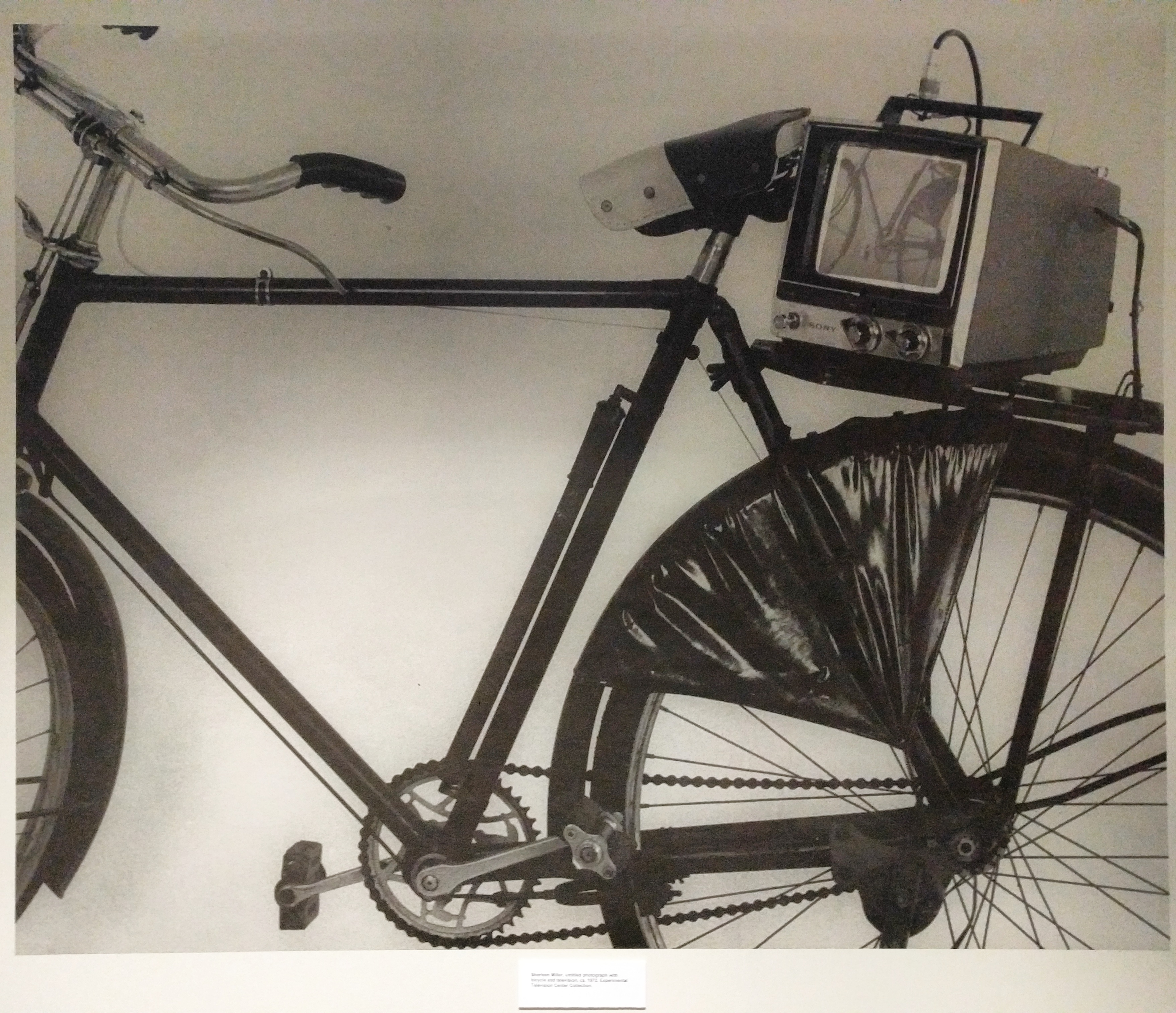 Black and white photo of a Sherry Miller Hocking media artwork: a bicycle with a portable CRTV attached to the back fender.