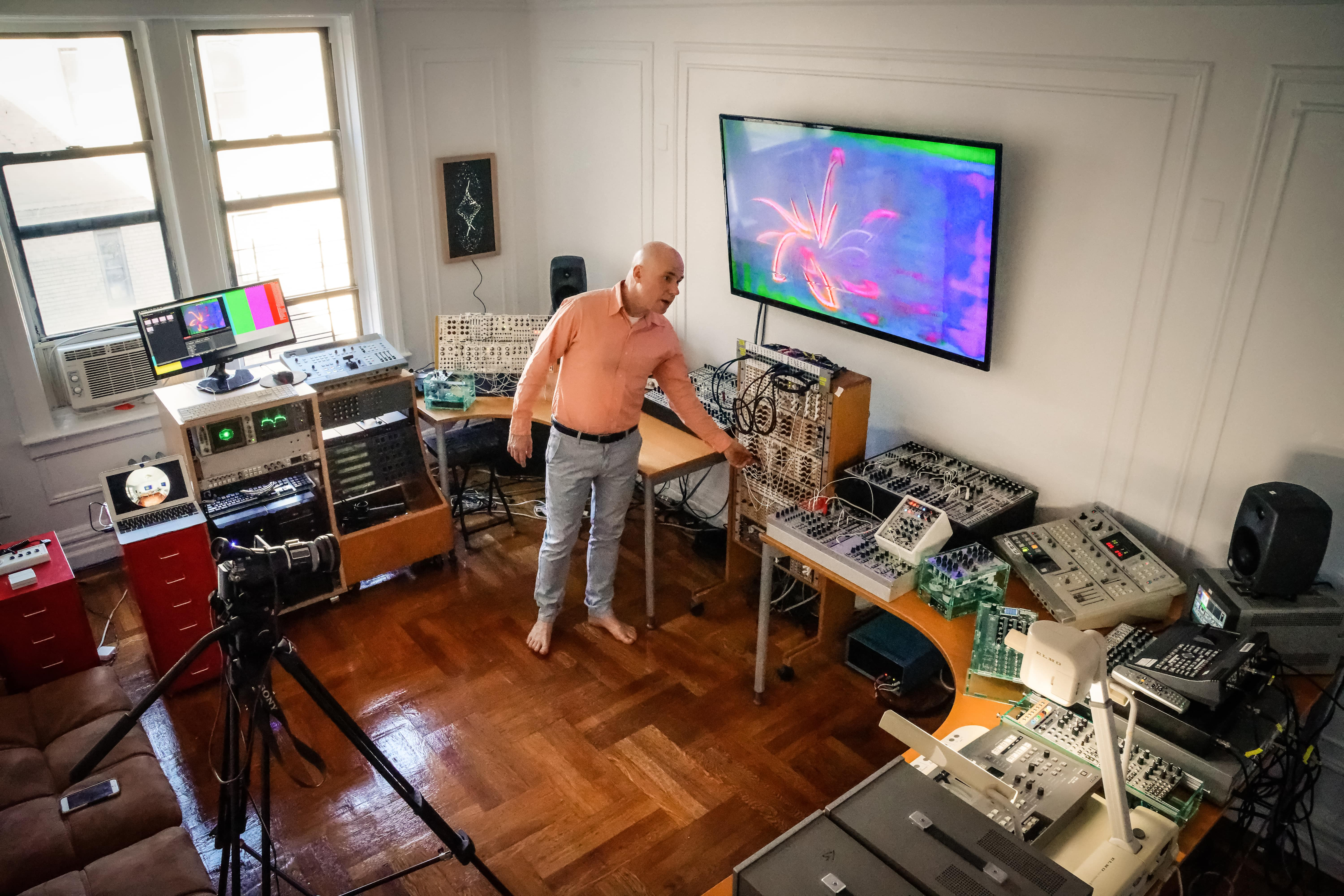 Media artist Benton C Bainbridge surrounded by unique video gear, seen from a high angle wide shot in his Bronx video synth studio, Shelterin' Place, in 2020. Photo by Corinne Laurice Pulicay