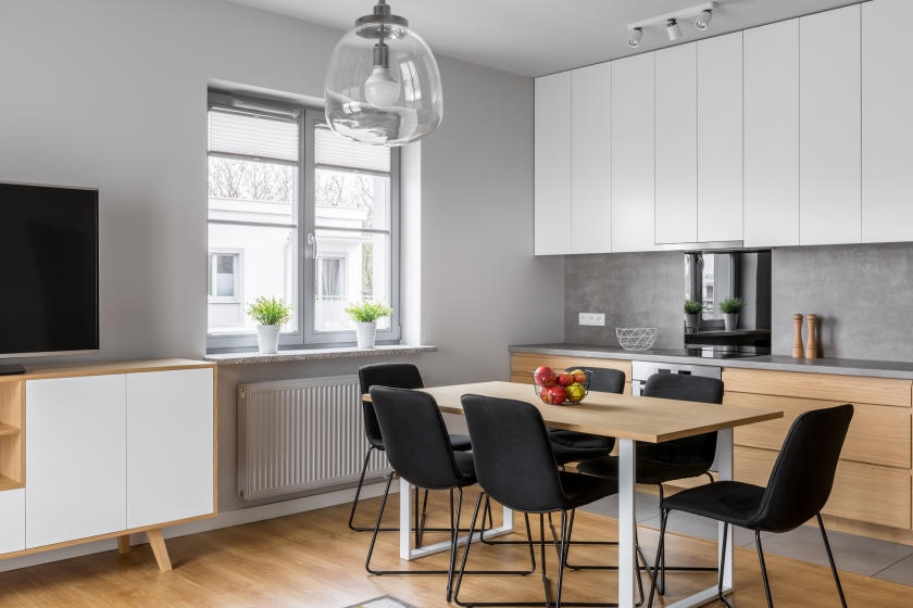 Kitchen and dining room with light gray wall and black accents