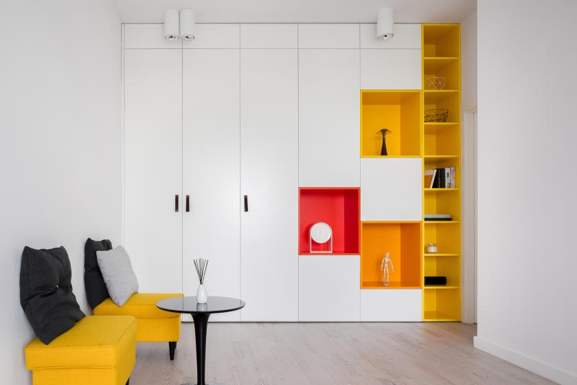 Small, white living room with yellow, orange, and red shelves