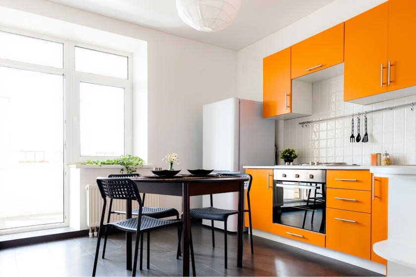 White kitchen and dining room with bright, orange cabinets