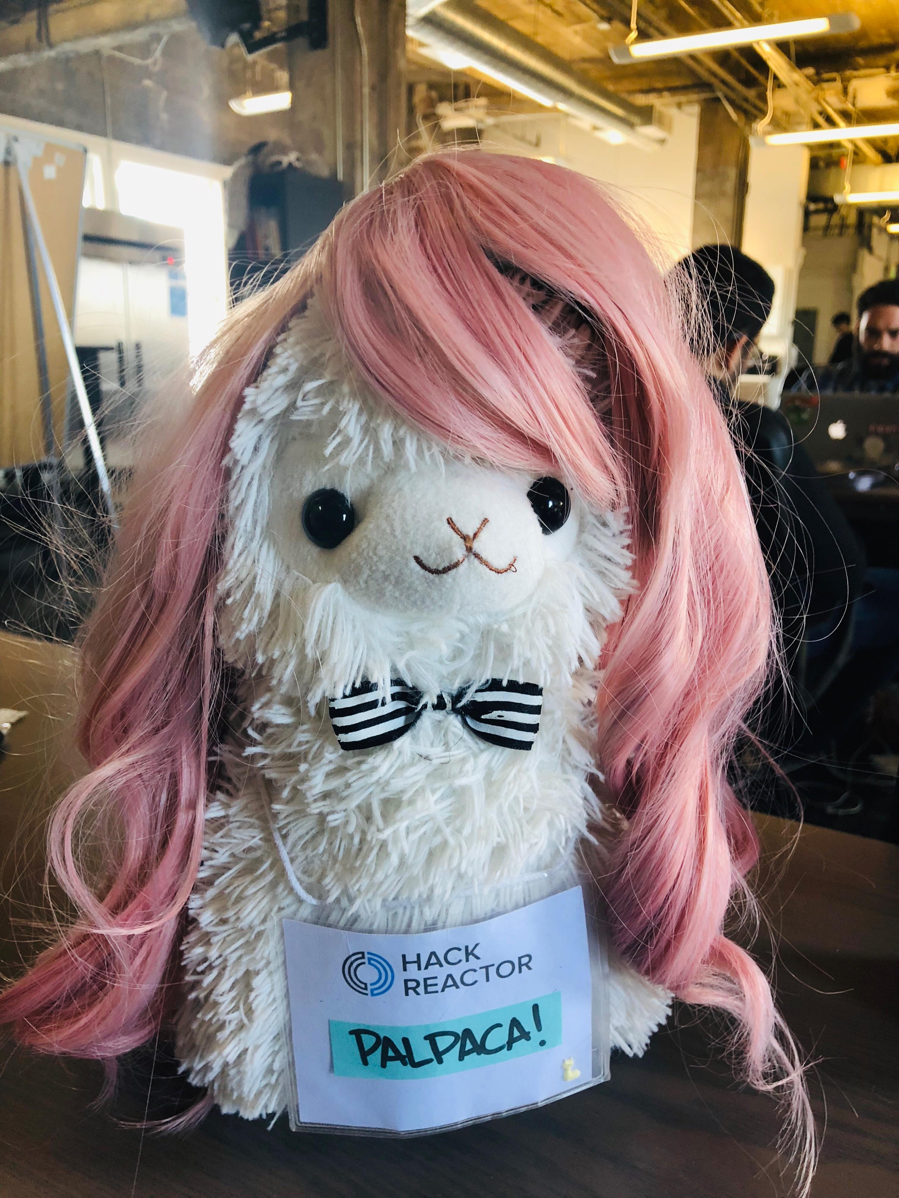 A plush alpaca wearing a pink wig