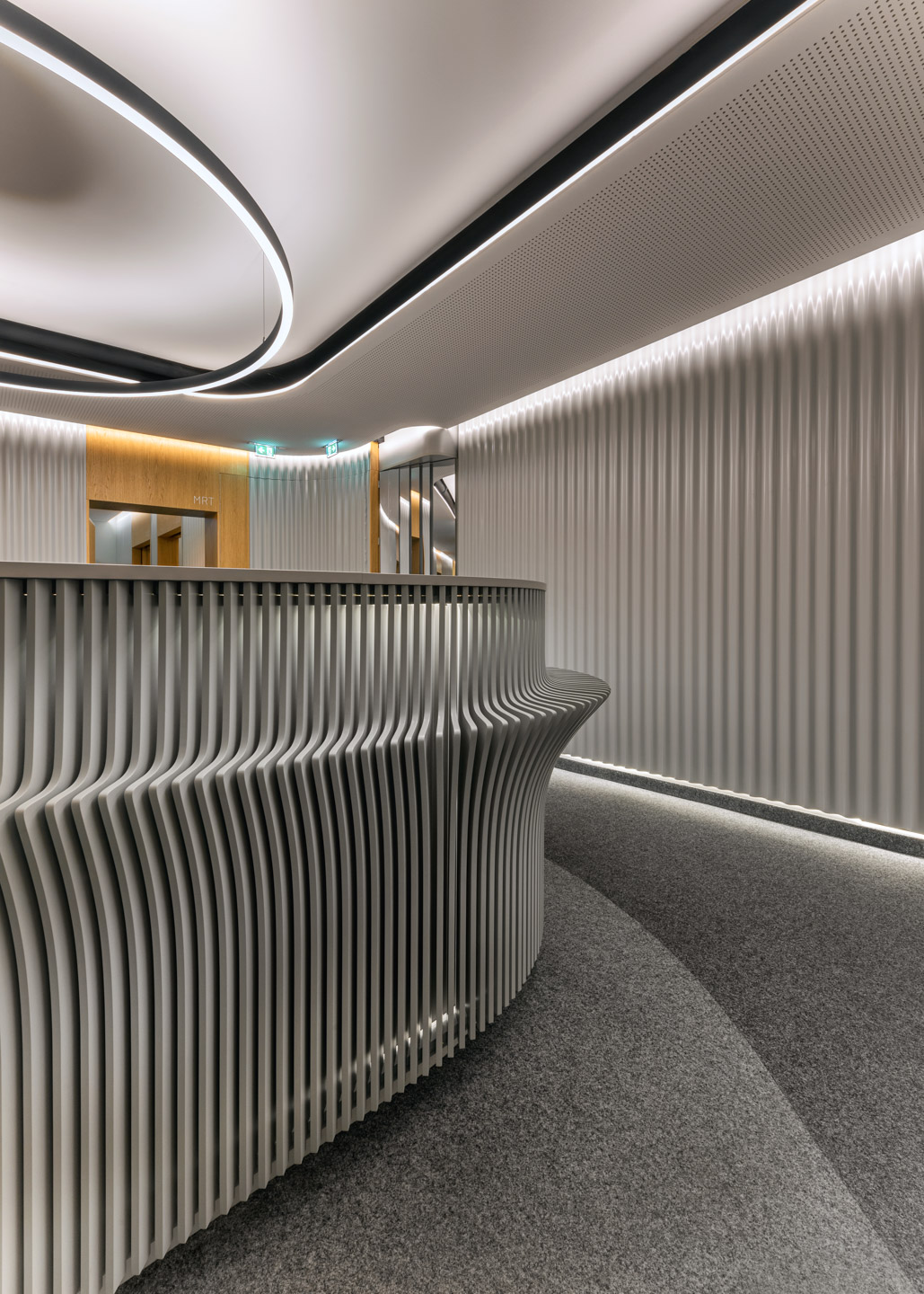Interior design with curved metal clad walls, concealed lighting and structured reception desk